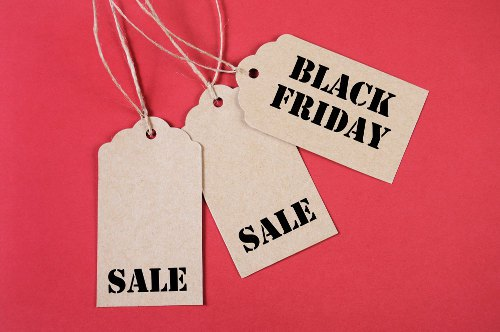 Black Friday Sale message sign on brown paper sale tags on red background.